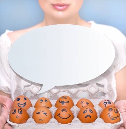 Portrait of young pretty business woman against grey background holding eggs with different emotions on their rawn faces. People management conceptual photo. photo