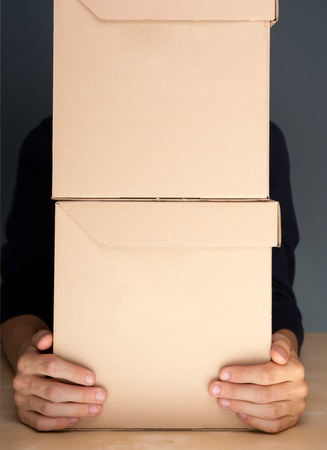 Successful Postal or delivery service concept. Man holding cardboard box with two arms on table photo