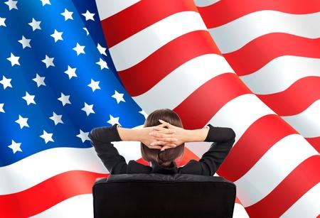 mujer de espaldas: Retrato de mujer de negocios linda joven sentada detr�s contra la bandera americana Foto de archivo