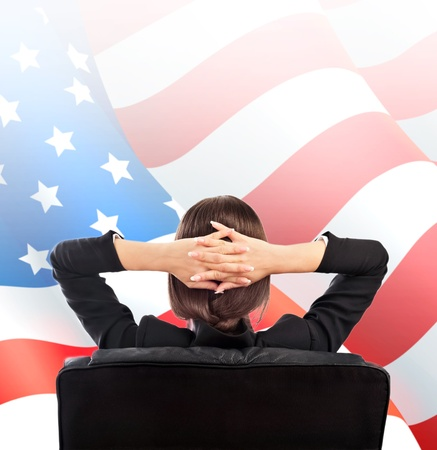 Closeup portrait of cute young business woman from behind sitting against American Flag. Copyspace photo