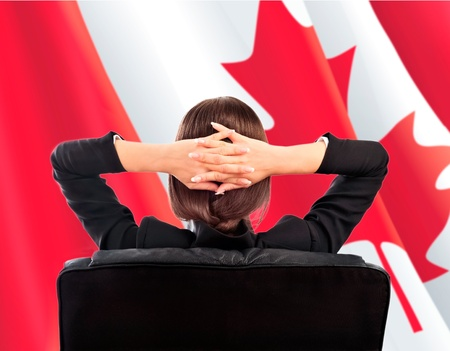 Closeup portrait of cute young business woman from behind sitting against Canadian Flag