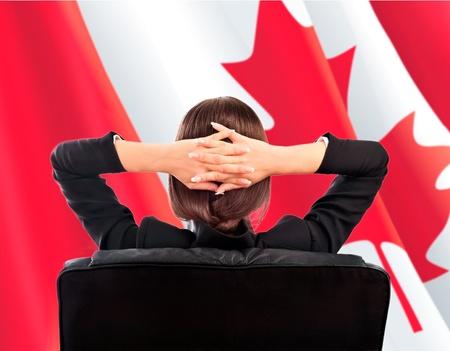 Retrato de mujer de negocios linda joven sentada detr�s contra Bandera de Canad�