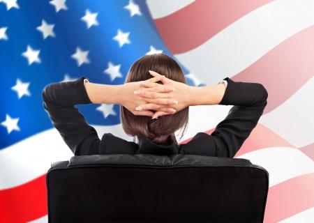 Retrato de mujer linda empresa joven desde atr�s que se sienta contra la bandera americana. Copyspace