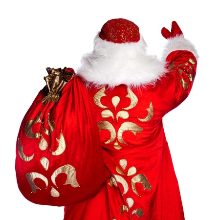 Santa Claus standing up on white background with his bag full of gifts. Photo from behind photo