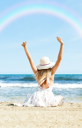 Portrait of young woman on the beach near the sea sitting with hands up wearing sophistical dress and hat looking at rainbow. Photo from behind photo