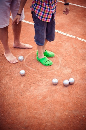 Artistic lifestyle photo of happy family: adult man and his son playing  petanque together at backyard near tennis court  photo