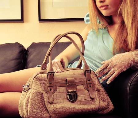 Close-up portret van de jonge mooie eenzame vrouw tot op de sofa binnen en hield haar luxe handtas Stockfoto