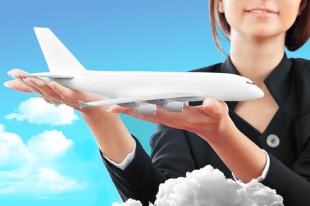 Retrato de joven azafata mujer feliz celebraci�n de aviones a reacci�n en sus brazos en primer plano. Anuncio banner para empresas de transporte Foto de archivo
