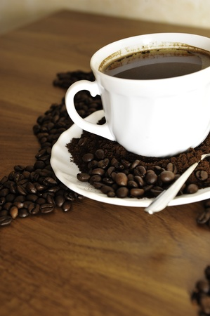 Dramatic photo of world map made of coffee beans. White cup with hot drink photo