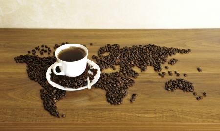 Dramatic photo of world map made of coffee beans. White cup with hot drink