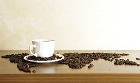 coffee crop: Dramatic photo of world map made of coffee beans. White cup with hot drink