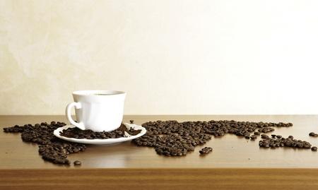 grains of coffee: Foto Dram�tico de mapa del mundo hecho de granos de caf�. Blanco taza de bebida caliente Foto de archivo