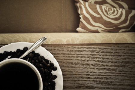 warm cup of coffee on brown background standing on sofa photo