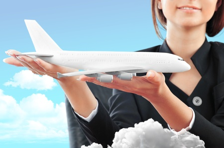 stewardess: Portrait of young happy woman stewardes holding jet aircraft in her arms on foreground. Advertisement banner for transport companies Stock Photo