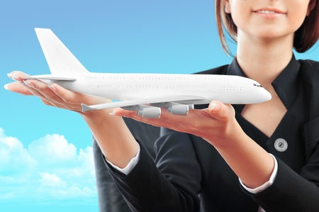 Portrait of young happy woman stewardes holding jet aircraft in her arms on foreground. Advertisement banner for transport companies Stock Photo