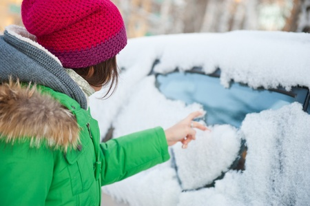 Beauty woman in the winter clothes drawing heart on car photo