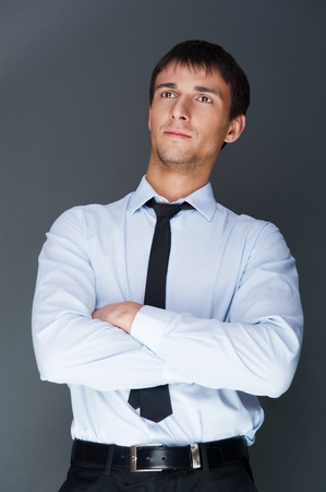 Closeup of a young smiling business man standing confidently against gray background photo
