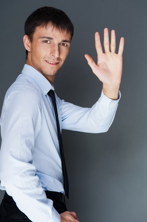 Closeup of a young smiling business man standing confidently against gray background and waving his hand photo