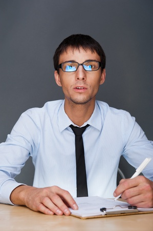 Portrait of an adult business man sitting in the office and signing documents Stock Photo - 27087481