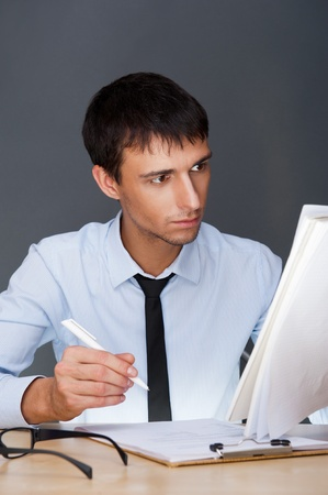 Portrait of an adult business man sitting in the office and signing documents Stock Photo - 27087492