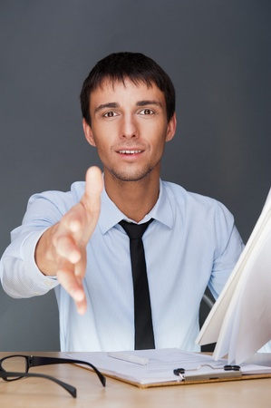 Portrait of an adult business man sitting in the office and holding contract and giving handshake Stock Photo - 27087494