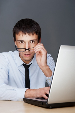 Portrait of a adult excited business man sitting by his laptop in the office and looking at camera expecting something Stock Photo - 27087504