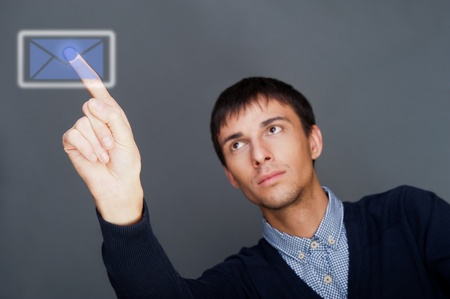 Portrait of adult business man pressing a touchscreen button while sitting at his office and working with his high-tech computer photo