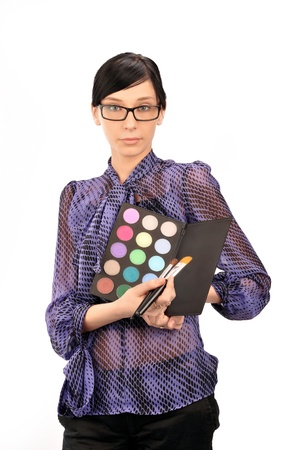 visagiste: Closeup portrait of young woman professional visagiste holding brushes and eyeshadows in her arms wearing glasses and thinking about she`s new idea. Isolated on white background