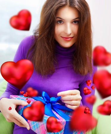 beanbag: Delighted woman opening a gift sitting on the bean bag at home and beautiful red heart shapes are flying around. Valentine`s day concept poster