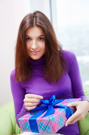 beanbag: Delighted woman opening a gift sitting on the bean bag at home