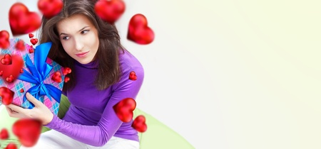 beanbag: Delighted woman opening a gift sitting on the bean bag at home and beautiful red heart shapes are flying around. Valentine`s day concept poster. Lots of Copyspace Stock Photo