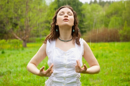 Closeup portrait of a beautiful young caucasian woman outdoor standing  under rain with open arms, breathing fresh air. Horizontal shot