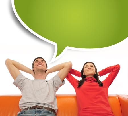 soñando: Primer retrato de una pareja adulta sentada en su sofá en su apartamento y soñar con algo. Globo blanco en la parte superior de la foto para el texto. Planificación de concepto de futuro Foto de archivo