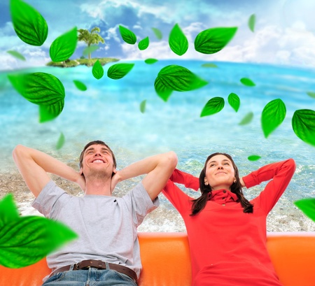 Closeup portrait of adult couple sitting on their sofa at their apartment and dreaming about something  Blank balloon at the top of the photo for your text  Planning future concept Grean leaves are floating around them photo