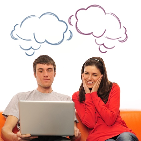 Smiling beautiful couple sitting on a sofa using laptop and dreaming about new home photo