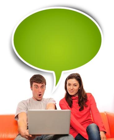 surprising: Portrait of a young couple using a computer. Isolated white background. Stock Photo