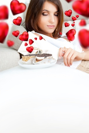 Portrait of young pretty woman eating tasty cakes on Valentines Day and graphic hearts are flying around her photo