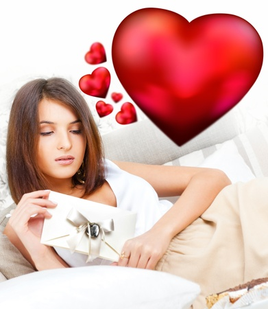 Cute young woman holds a valentine and reading it. Beautiful heart symbols flying around her. She is in love with her couple Stock Photo - 27090587