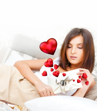 Cute young woman holds a valentine and reading it. Beautiful heart symbols flying around her. She is in love with her couple Stock Photo - 27090590