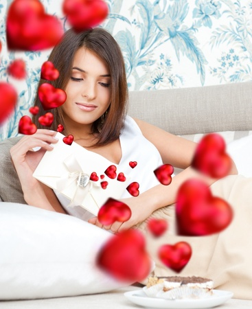 Cute young woman holds a valentine and reading it. Beautiful heart symbols flying around her. She is in love with her couple photo