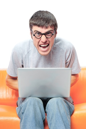 Closeup portrait of funny handsome young relaxing man using laptop and sitting on the sofa, wearing round glasses.  photo