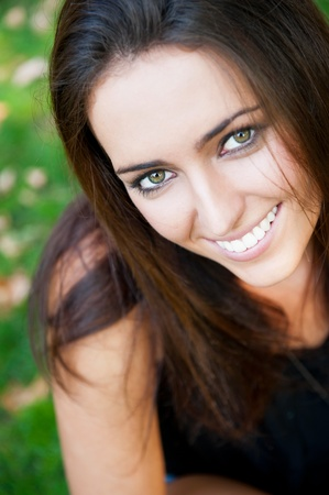 Portrait of smiling young girl sitting on grass in the forest and looking at you photo