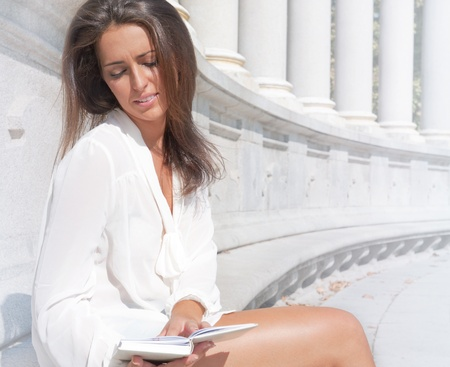 Beautiful dark-haired pretty girl in jeans and white blouse reads white book against Renaissance building of museum or galery photo