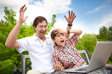 Closeup portrait of happy family: father and his son using laptop outdoor at their backyard sitting on the bench photo