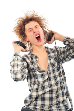 Portrait of funny young man with awesome hairdo isolated on white background. Listening music using headphones photo