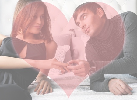 Fashion style photo of an attractive young couple inside luxury aristocratic interior of their apartment  Man making proposal to his girlfriend and giving a ring to her  Heart shape with copyspace in foreground photo