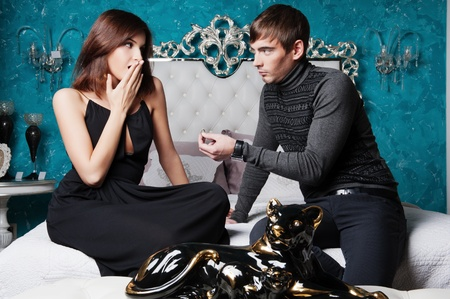 Fashion style photo of an attractive young couple inside luxury aristocratic interior of their apartment. Man making proposal to his girlfriend and giving a ring to her photo