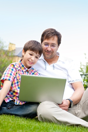 Closeup portrait of happy family: father and his son using laptop outdoor at their backyard sitting on the grass together photo