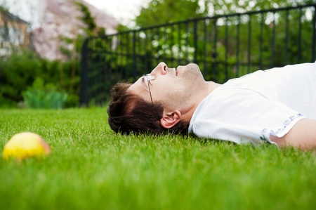 Close-up portrait of young good looking man in white shirt lying on lawn and daydreaming photo