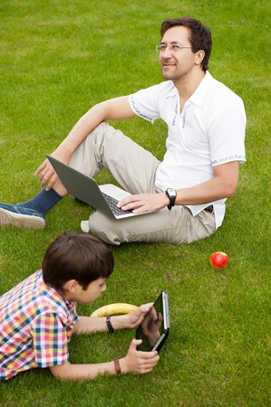 Man and young boy his son sitting outdoors on their backyard using their computers with wireless internet  and smiling photo